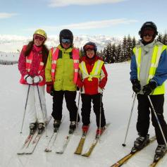 4 skiers stood at the top of a mountain smiling.