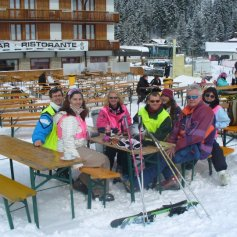 Group of people sat on benches in the snow.