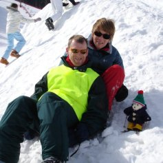 People sledging with a little woolly polar bear.