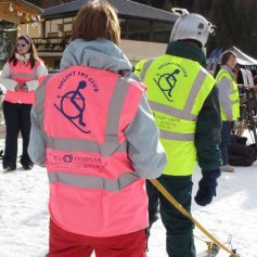 Guide leading disabled skier.