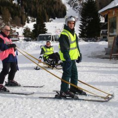 Guide leading disabled skier with tethers attached to the tips of the skis.