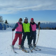 Disabled skier and 2 Guides stood at the top of a mountain.