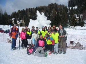 Group of people on the trip, stood in front of a snow sculpture in the shape of a cow.