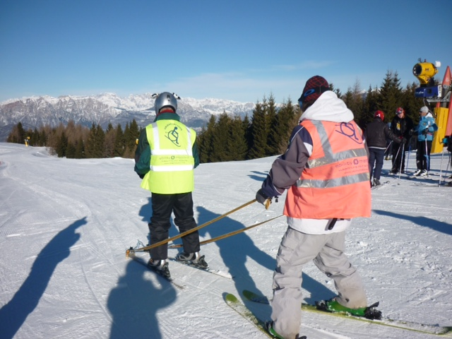 Disabled skier skiing with a Guide attached to their skis by tethers.