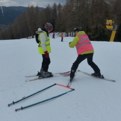 Guide demonstrating skiing technique to a disabled skier.