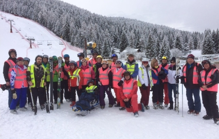 group of skiers, guides, and helpers stood in the snow at the bottom of a mountain.